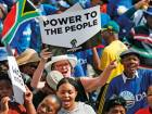 """People hold anti-Zuma banners during a rally organised by the newly formed """"Freedom Movement"""" which comprises of opposition parties, religious community and civil society, at Caledonian Stadium on Thursday in Pretoria."""