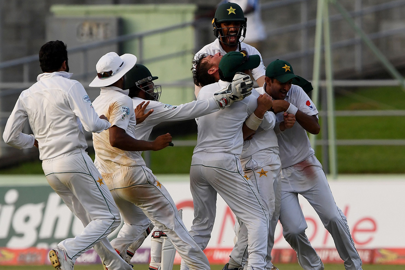 Members of the Pakistan cricket team celebrate with final wicket taker Yasir Shah (C) after winning