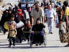 A displaced Iraqi man pushes his mother in a wheelchair during a battle between Iraqi forcesand Islamic State militants in western Mosul, Iraq on Wednesday.