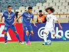 Al Ain's Omar Abdul Rahman (right) attempts to take the ball past Esteghlal's Mojtaba Haghdust (centre) during their match at the Azadi Stadium in Tehran.