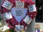 A heart-shaped wreath covered with positive messages hangs on a traffic light pole at a memorial for two bystanders who were stabbed to death, while trying to stop a man who was yelling anti-Muslim slurs and acting aggressively toward two young women on a light-trail train in Portland.