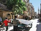 A man pushes an iron cart loaded with solar panels in the rebel-held town of Douma on the outskirts of the capital Damascus.