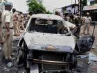 Policemen inspect a vehicle that was set ablaze by farmers during the protest on the outskirts of Mumbai.