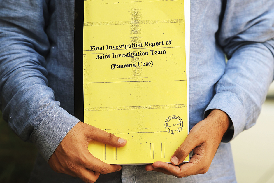 A Pakistani journalist poses for a photograph with a copy of a corruption report