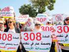 Women activists protest in front of Jordan's parliament in Amman with banners calling on legislators to repeal a provision that allows a rapist to escape punishment if he marries his victim.