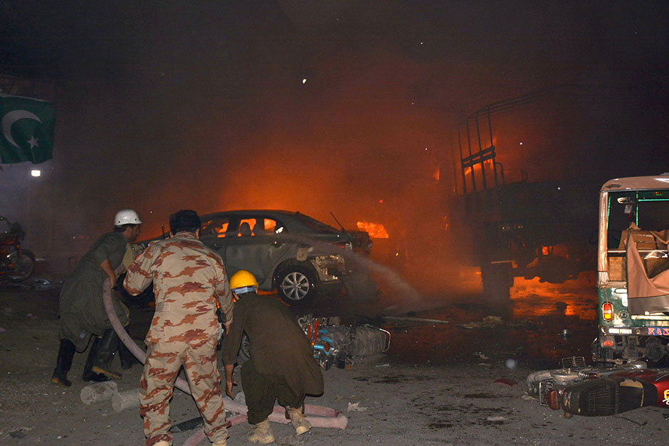 Firefighters use hoses to try to extinguish burning vehicles after a blast in Quetta
