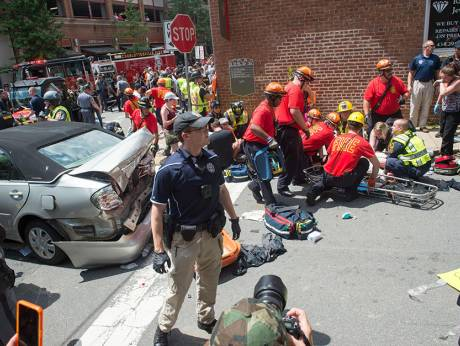 A woman receives first-aid after a car ploughed into a crowd of protesters