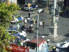 Injured are helped by responders as a tour bus passes by after a white van jumped the sidewalk in the historic Las Ramblas district of Barcelona, Spain, crashing into a summer crowd of residents and tourists Thursday, Aug. 17, 2017.