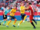 Atletico de Madrid's forward Antoine Griezmann (centre) vies with Girona's Bernando Espinosa during the Spanish league match at the Montilivi stadium.