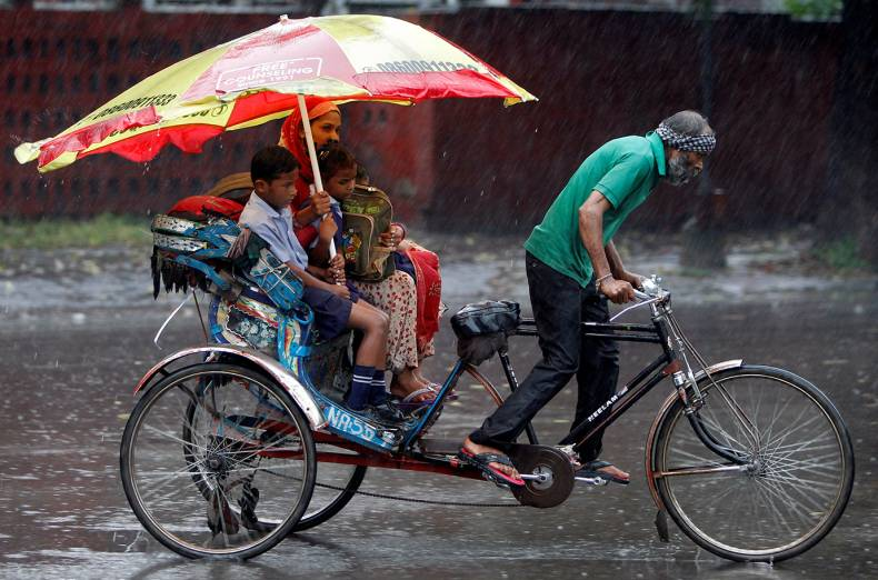 a-woman-and-her-children-ride-in-a-rickshaw-during-heavy-rains-in-chandigarh-india