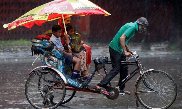 A woman and her children ride in a rickshaw during heavy rains in Chandigarh, India