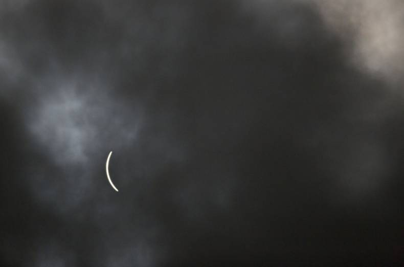 A sliver of the sun remains visible through a passing cloud during a solar eclipse as seen from a viewing event on the campus of Southern Illinois University (SIU) in Carbondale, Illinois, U.S., on Monday, Aug. 21, 2017.