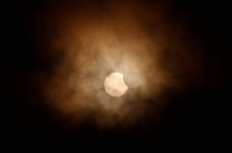 The partial eclipse is obscured by clouds, viewed from the flight deck of the Naval museum ship U.S.S. Yorktown during the Great American Eclipse in Mount Pleasant, South Carolina, U.S. August 21, 2017.