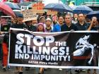 Protesters display a banner as they march to join the wake for slain Kian Loyd Delos Santos who was killed in a shootout with police.