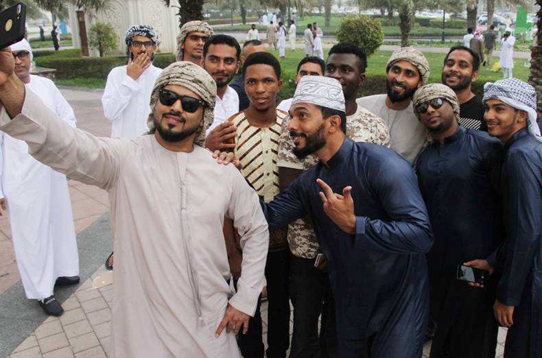a-group-of-men-pose-for-a-selfie-at-the-sharjah-corniche