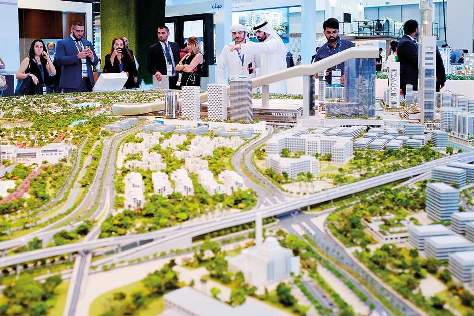 Exhibitors interact with visitors near the District One project displayed at the Meydan stand
