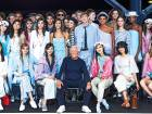Italian designer Giorgio Armani poses for a photograph next to models after the fashion house Emporio Armani catwalk show for the Spring/Summer 2018 collection on the third day of The London Fashion Week Women's in London on September 17, 2017.