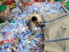 A worker sorts bottles to throw them in a plastic bottle chipper at a recycling workshop in Islamabad, Pakistan