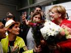 Syrian refugees offer flowers to Merkel after she gave a speech during an election rally in Schwerin, northern Germany, on September 19, 2017. Germany goes to the polls for parliamentary elections on September 24, 2017.