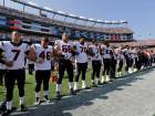 Members of the Houston Texans team stand with arms locked during the national anthem before an NFL f
