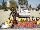 An Afghan officer walks next to containers filled with explosive material, after presenting the seized haul to the media, at the National Directorate of Security headquarters in Kabul.