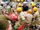 Rescue workers carry the body of a victim at the site of a building collapse in Bangalore, India. A two-story building collapsed early Monday when a cooking gas cylinder exploded in a residential building in southern India.