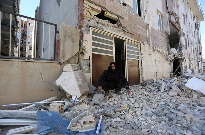 a-man-sits-outside-a-damaged-belonging-following-an-earthquake-in-sarpol-e-zahab-county-in-kermansha