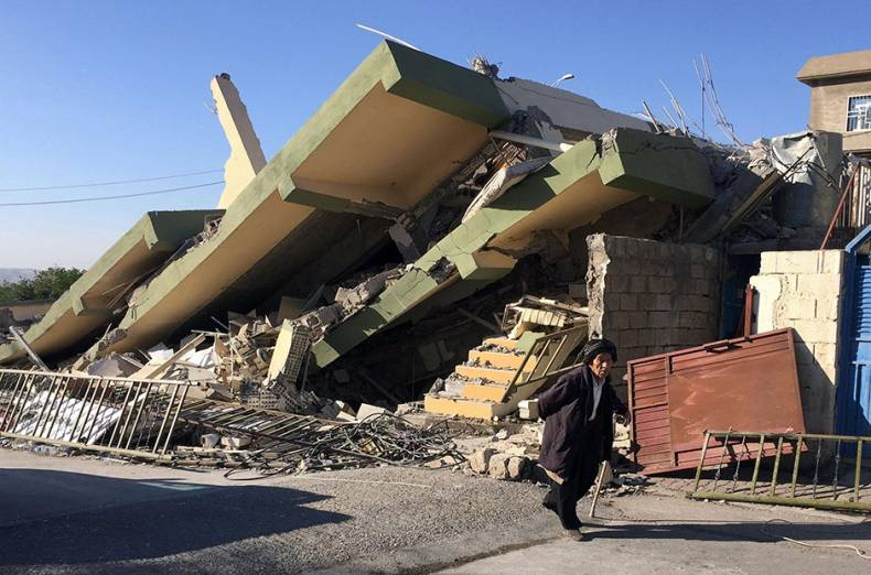 a-man-walks-past-a-damaged-building-following-an-earthquake-in-darbandikhan-in-sulaimaniya-governora