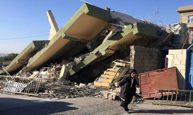A man walks past a damaged building following an earthquake in Darbandikhan in Sulaimaniya Governora