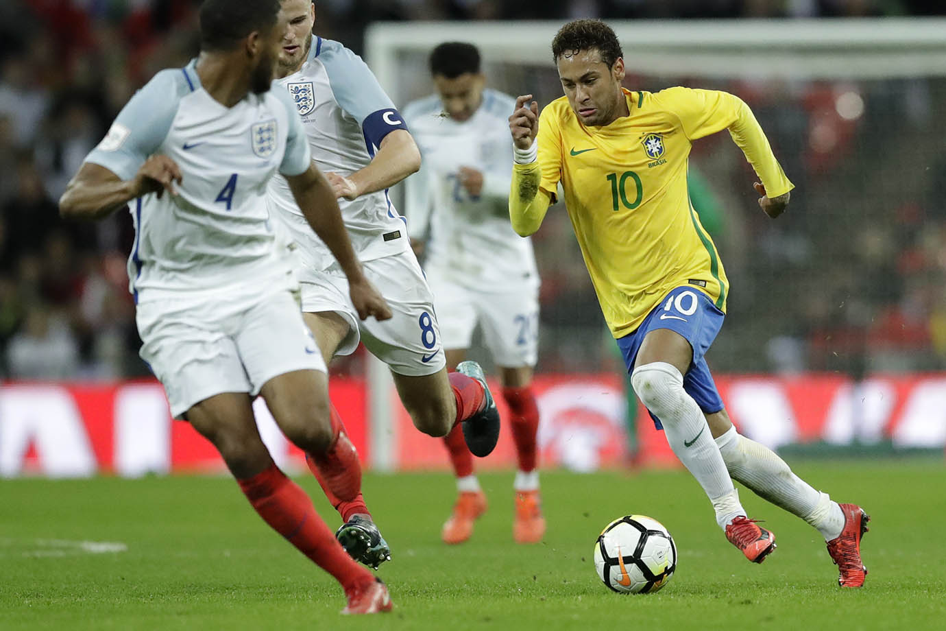 Brazil's Neymar takes the ball forward watched by England's Joe Gomez, left, and Eric Dier.
