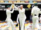 Australia's Nathan Lyon celebrates with Peter Handscomb (left) after claiming the wicket of England's Chris Woakes during the first Ashes test in Brisbane.