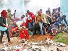 People fall as police fire tear gas to control a crowd trying to force their way into a stadium to attend the inauguration of President Uhuru Kenyatta at Kasarani Stadium in Nairob.