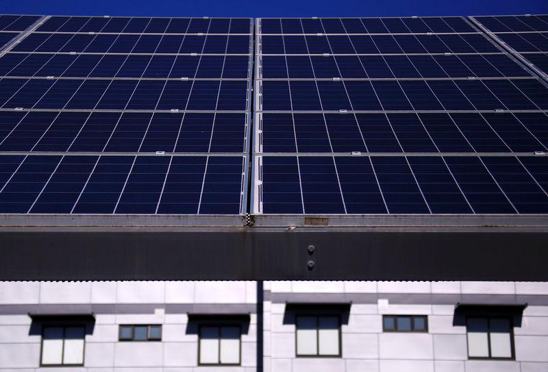 A solar array, a linked collection of solar panels, can be seen in front of a residential apartment