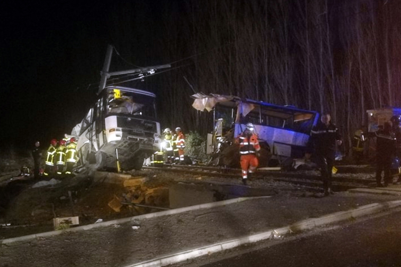 Rescue workers help after a school bus and a regional train collided in the village of Millas, south