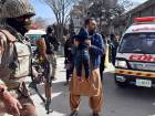 A man carries a boy as he shouts for an ambulance after gunmen attacked a Methodist Church in Quetta.