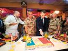 Macron cuts a cake in the colours of the French flag, cooked by French soldiers of the air force base of the Barkhane force, as he celebrates his 40th birthday on Friday.