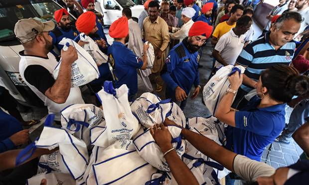 Turbaned riders donate food to workers in camps