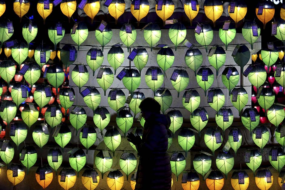 A woman prays in front of lanterns