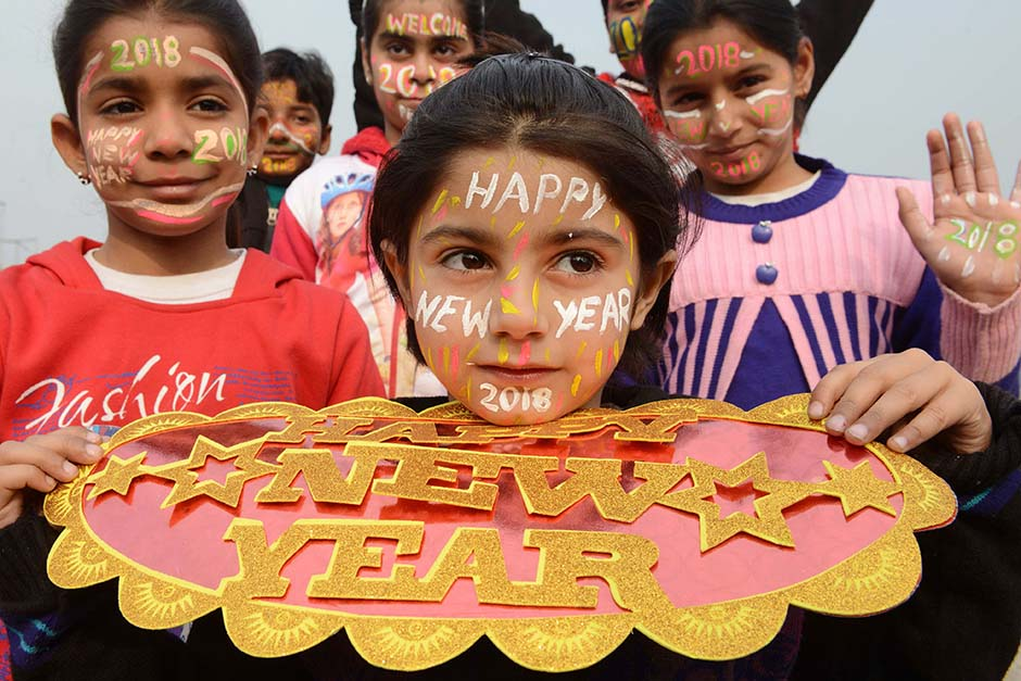 Indian children with their faces painted pose for a picture to welcome the New Year 2018 in Amritsar