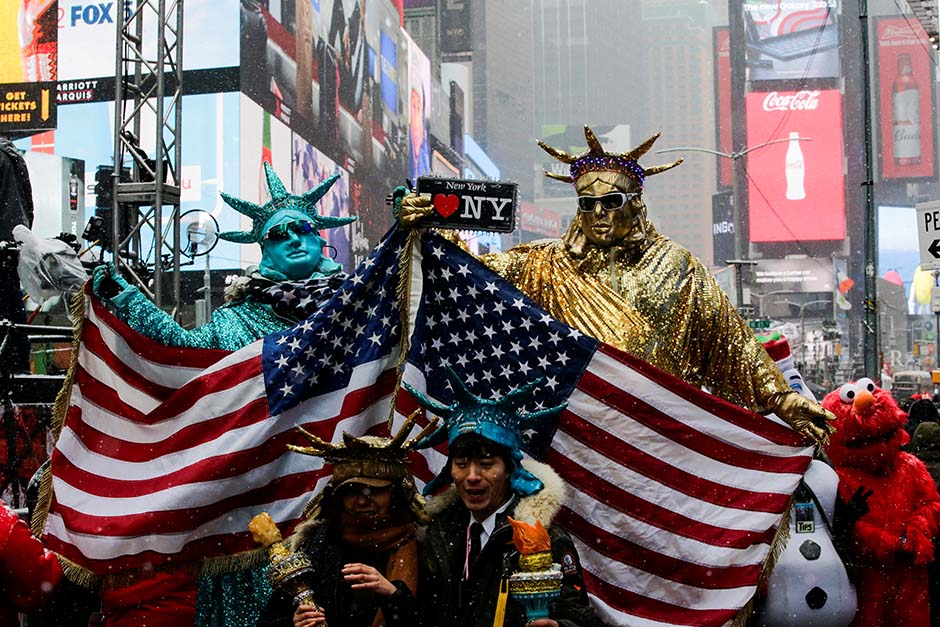 People dressed up as Statues of Liberty pose for pictures at Times Square