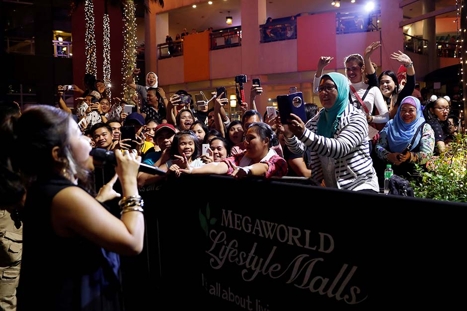 A singer entertains the crowd during a New Year's eve countdown party at Eastwood mall in Quezon Cit