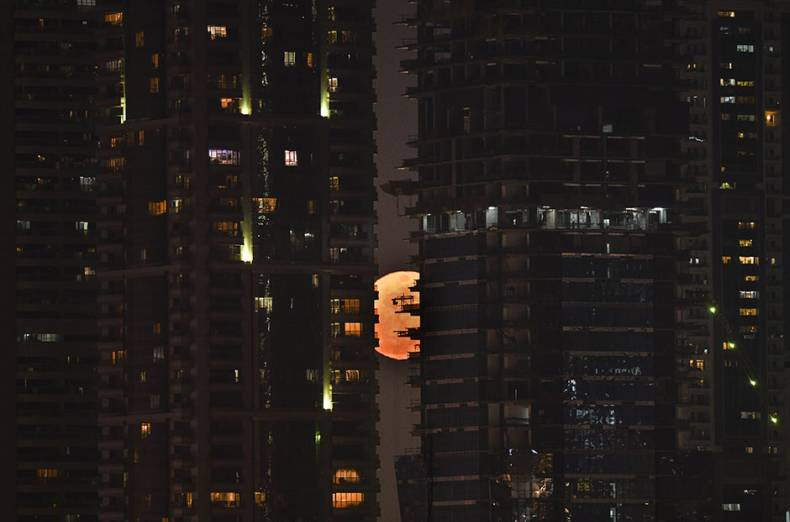 supermoon-is-seen-behind-the-high-rise-towers-in-dubai