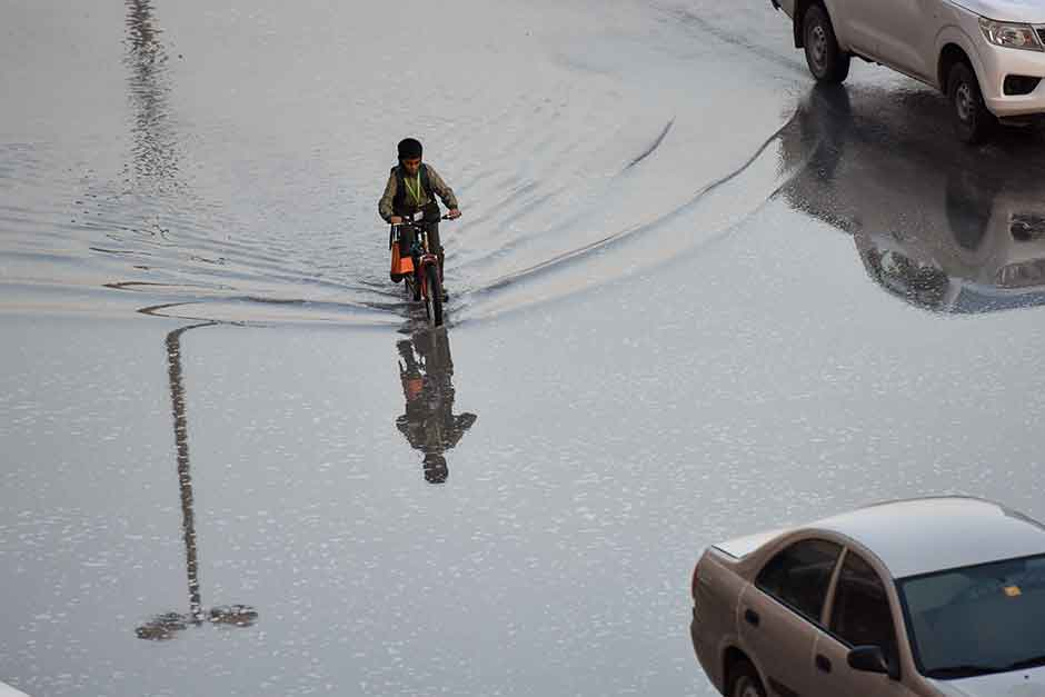 A child wades through a flooded road in Sharjah after the overnight rain