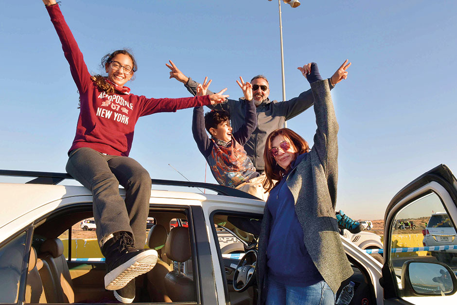 A family atop their vehicle in a jubilant mood