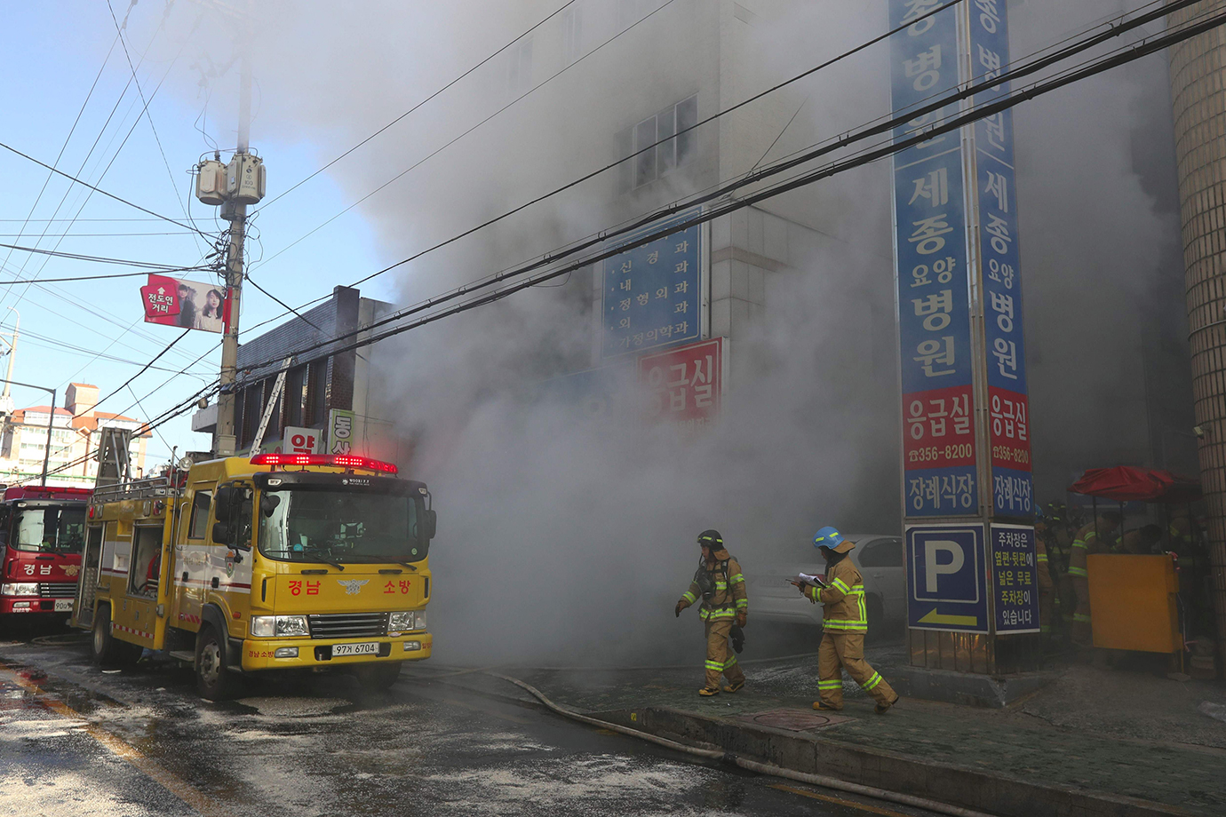 Firefighters try to put out a fire at a hospital building engulfed by heavy grey smoke in Miryang on
