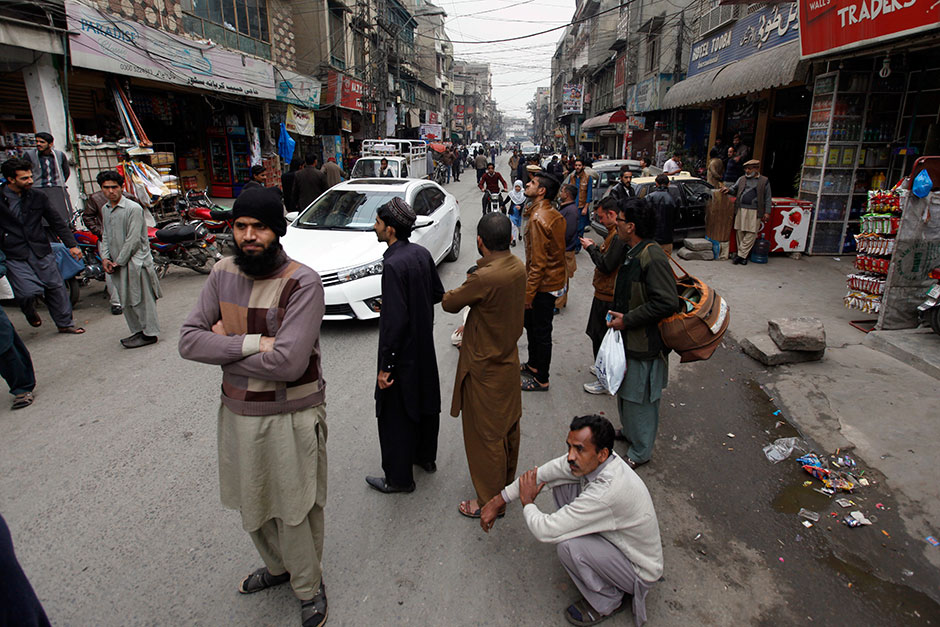 People stand outside their shops after a severe earthquake is felt in Rawalpindi, Pakistan