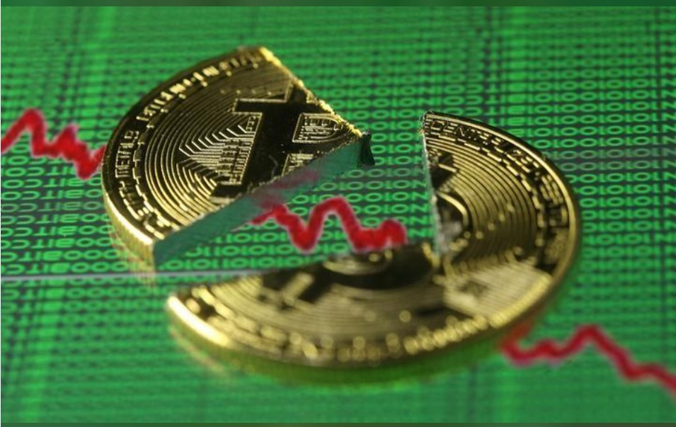 Broken representation of the Bitcoin virtual currency, placed on a monitor that displays stock graph