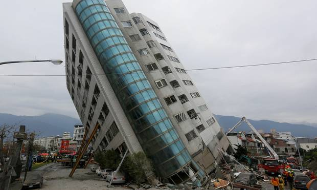 Rescue workers are seen by a damaged building after an earthquake hit Hualien