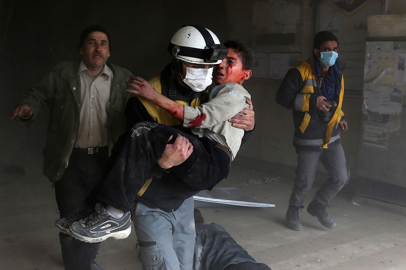 A member of the Syrian civil defence carries a wounded child from the rubble after a reported regime