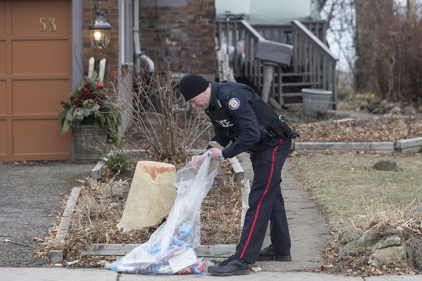 A police officer is shown outside a house on Mallory Crescent in Toronto, where Bruce McArthur did l